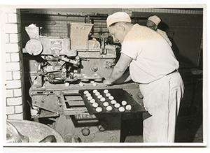 Helens morbror, bagaren Olle, lägger bullar på bullplåt.